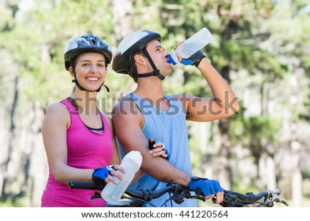Portrait of young woman with man riding bicycle at forest - stock photo
