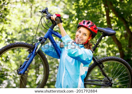 Portrait of young woman with mountain bike on shoulder.