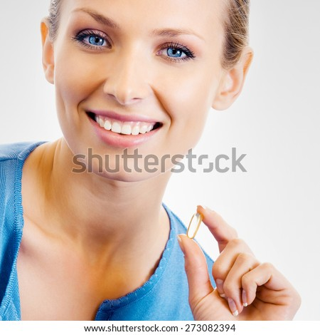 Portrait of young woman with Omega 3 fish oil capsule, over grey background - stock photo