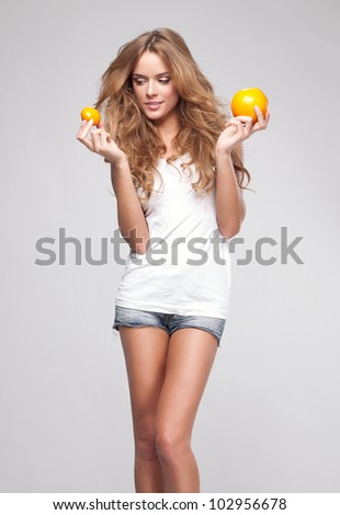 Portrait of young woman with orange - stock photo