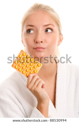 Portrait of young woman with pills - stock photo