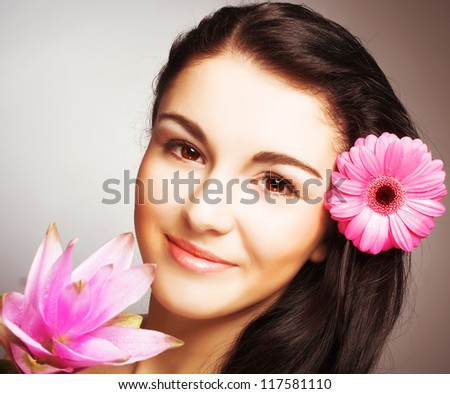 Portrait of young woman with pink flowers