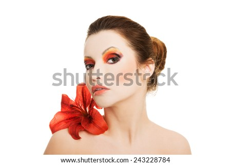 Portrait of young woman with red lily flower.