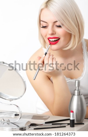 Portrait of Young Woman With Red Lips. Beautiful Woman Doing Daily Makeup. Lipstick applying