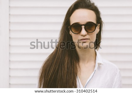 portrait of young woman with retro round sunglasses  - stock photo