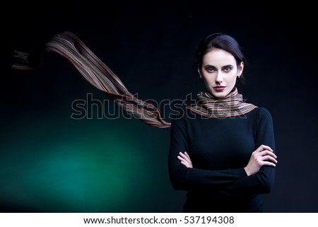 Portrait of young woman, with scarf fluttering. Studio shot