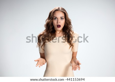Portrait of young woman with shocked facial expression over gray background - stock photo