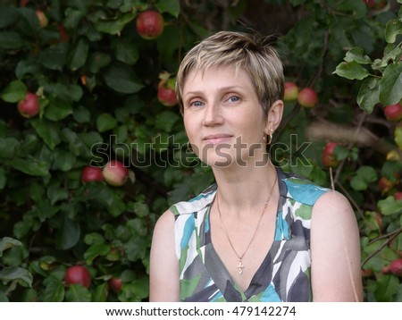 portrait of young woman with short hair beside an apple tree