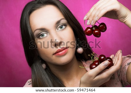 Portrait of young woman with sweet cherries