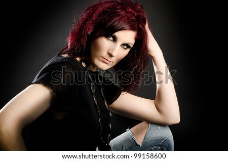 Portrait of young woman with torn jeans and red hair - stock photo
