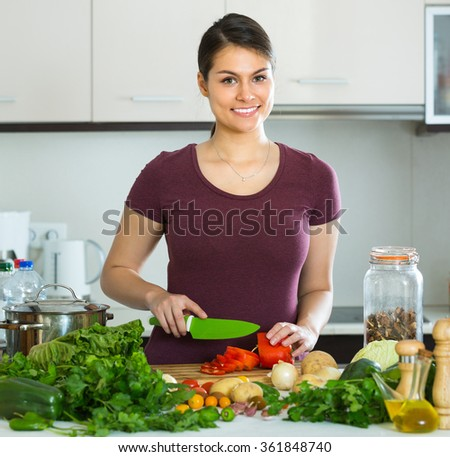 Portrait of young woman with vegetables at kitchen table