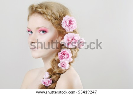 Portrait of young woman with with braids and flowers in hair - stock photo