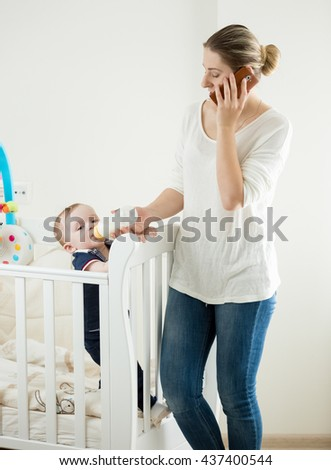 Portrait of young woman working at home and talking by phone while feeding her baby - stock photo