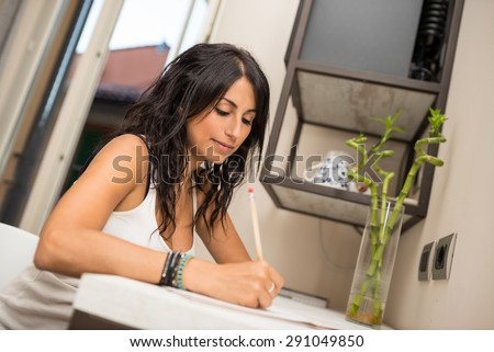 Portrait of young woman writing a letter in hotel room. - stock photo
