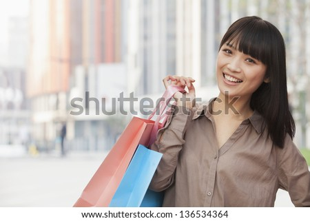 Portrait of young women holding shopping bags outdoors, Beijing