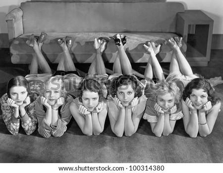 Portrait of young women in row on floor - stock photo