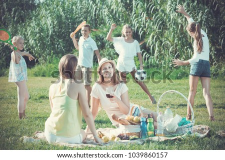 Portrait of young women on picnic in summer park with happy children playing behind