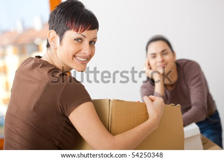 Portrait of young women packing up cardboard boxes. Looking at camera, smiling. - stock photo
