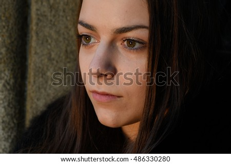 Portrait of young worried girl with big dark brown eyes looking away closeup