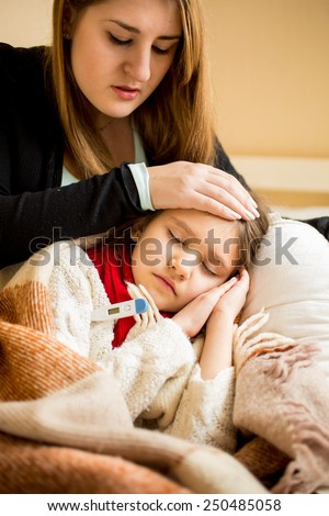 Portrait of young worried mother checking sick daughters temperature - stock photo