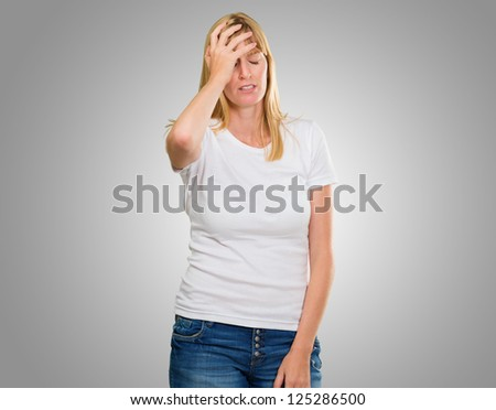 Portrait Of Young Worried Woman against a grey background - stock photo