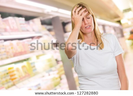 Portrait Of Young Worried Woman at the supermarket - stock photo