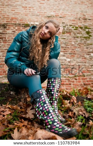Portrait of young worried woman in rubber boots - autumn lifestyle - stock photo