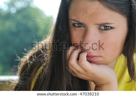 Portrait of young worried woman (teenage girl) in depression outdoors - stock photo