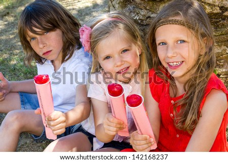 Portrait of youngsters enjoying ice pops outdoors.
