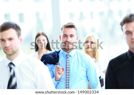 Portrait of yung handsome businessman which stand in center his team - stock photo