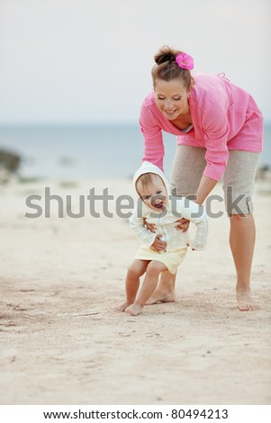Portrait ofl young happy mother with child at the beach - stock photo