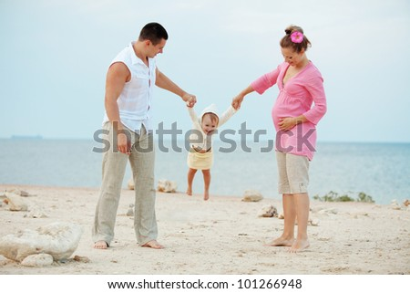 Portrait ofl young happy parents with child at the beach - stock photo