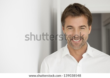 Portrait on a nice looking man with a toothy smile wearing a white shirt.This photography was made with a professional model and others professionals to reach this quality from a raw. - stock photo