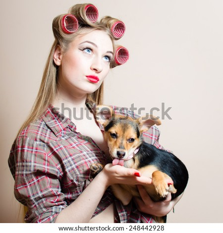 Portrait on beautiful blond young woman with blue eyes having fun with curlers on her head and a dog in her arms looking up at copy space background - stock photo
