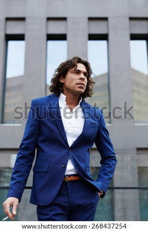 Portrait on handsome executive smoking cigarette near office before began his work day, worried and concerned business man standing outdoors - stock photo
