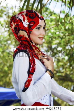 Portrait on side view of pretty young Muslim woman. - stock photo