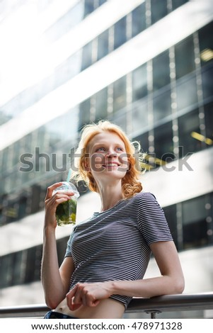 Portrait on urban background of slim hipster girl with mojito