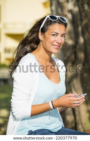 Portrait outdoors of an attractive young woman sitting with sun glasses on the top of her head. She is smiling and looking at camera with her smartphone. Head and shoulders. - stock photo