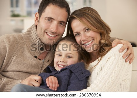 Portrait parents and daughter at home - stock photo