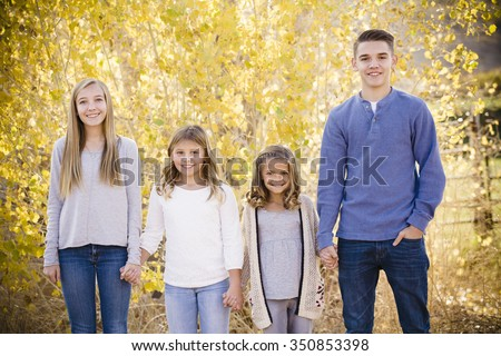 Portrait photo of Four cute kids holding hands together outdoors during an autumn day. Sibling group of three girls and boy of different ages - stock photo