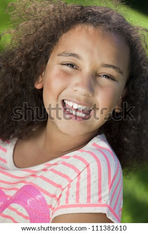 Portrait photograph of a beautiful young smiling happy mixed race interracial African American girl, shot outside in a park
