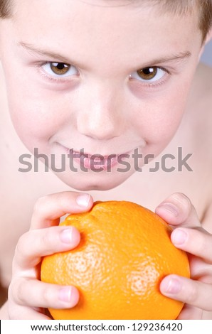 portrait photograph of a child with an orange Valencia in his hands