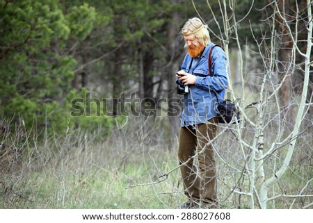 portrait photographer with a red beard and a mustache in a meadow in early spring  - stock photo