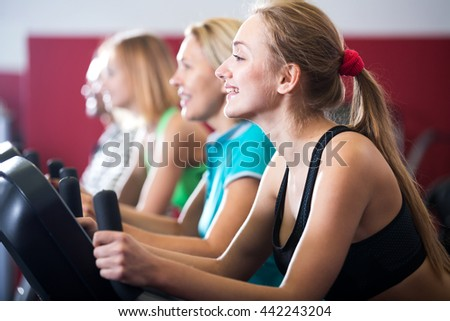 Portrait positive people training on exercise bikes together in gym
