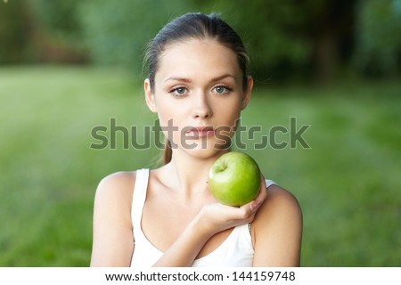 portrait pretty of woman with green apple . background summer park - stock photo