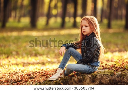 portrait. Pretty red-haired girl in the autumn park - stock photo