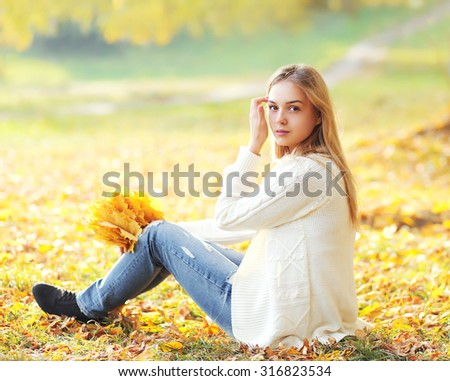 Portrait pretty woman with yellow maple leafs in autumn park - stock photo