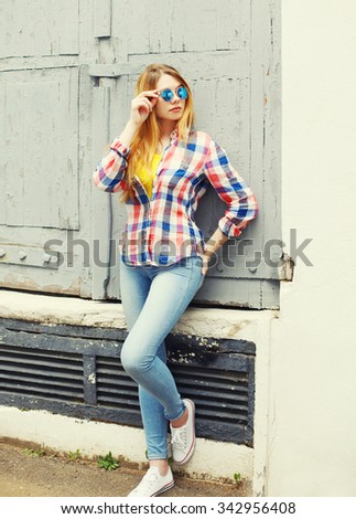 Portrait pretty young girl wearing a checkered shirt and sunglasses in city - stock photo