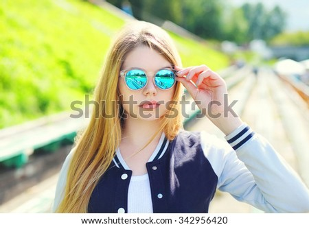 Portrait pretty young girl wearing a sport jacket and sunglasses in city