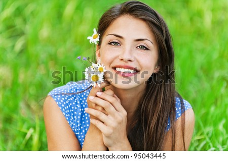 portrait pretty young long-haired woman holding bouquet wildflowers background green meadow - stock photo